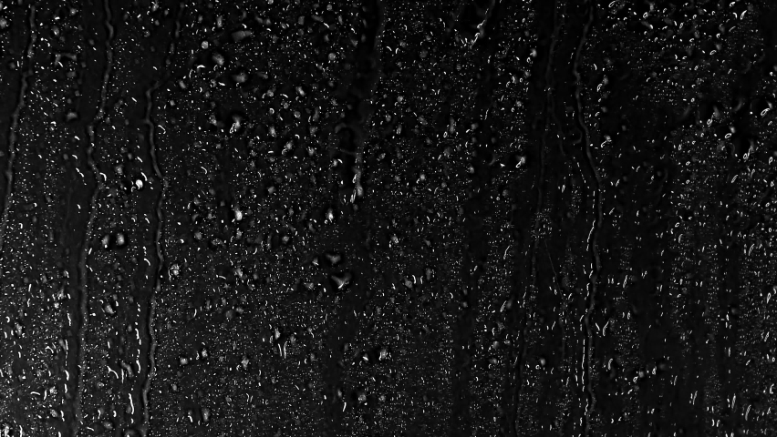 Water Drops following down on black background. Drops of Rain trickling down isolated. Best 4K footage Droplets of Water on Black Glass running down. Perfect for digital composing.