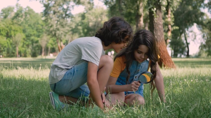 Little girl and boy in a park looking at the grass through a magnifying glass. Children playing outdoors and having fun.