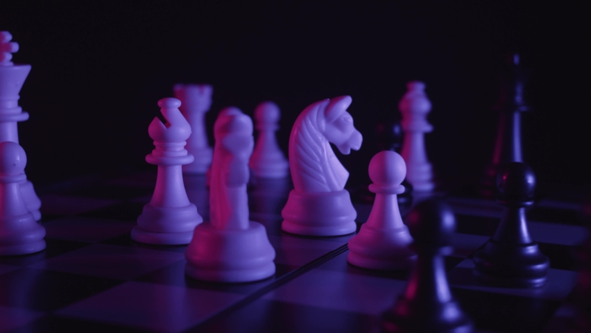 Chess pieces on a chessboard in a colorful fashion style. Studio neon light footage. Pink and purple colors. Slow tracking shot. Fashion, business concept. Depth of field, soft focus . Red camera | Shutterstock HD Video #1058648581