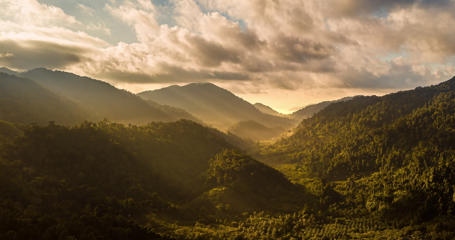 Aerial drone hyperlapse timelapse of beautiful tropical valley between mountains. The first rays of the rising sun break through the clouds and clouds. The last rays of the sunset hit the tree crowns.   Shutterstock HD Video #1058648860