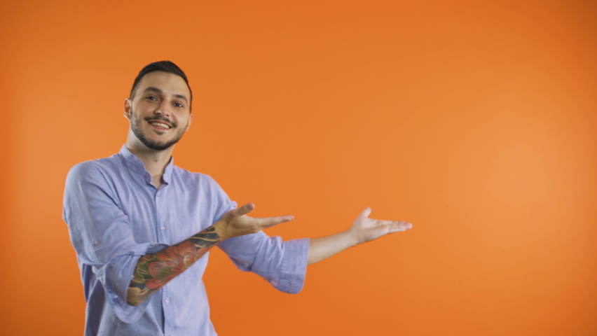 Young smiling man dancing and presenting to side with hands, isolated on orange background Royalty-Free Stock Footage #1058648989