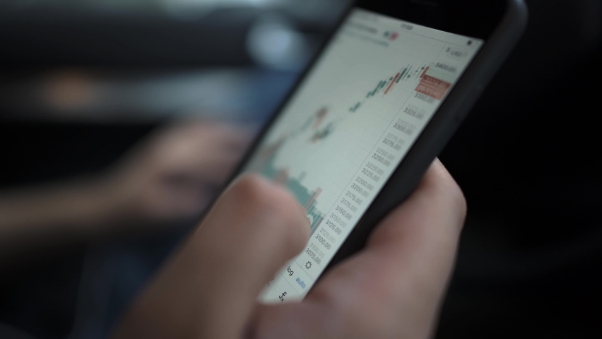 Hands with a mobile phone, checking stock market data. Scrolling through, touching stock market graph on a touch screen device close up Royalty-Free Stock Footage #1058658370