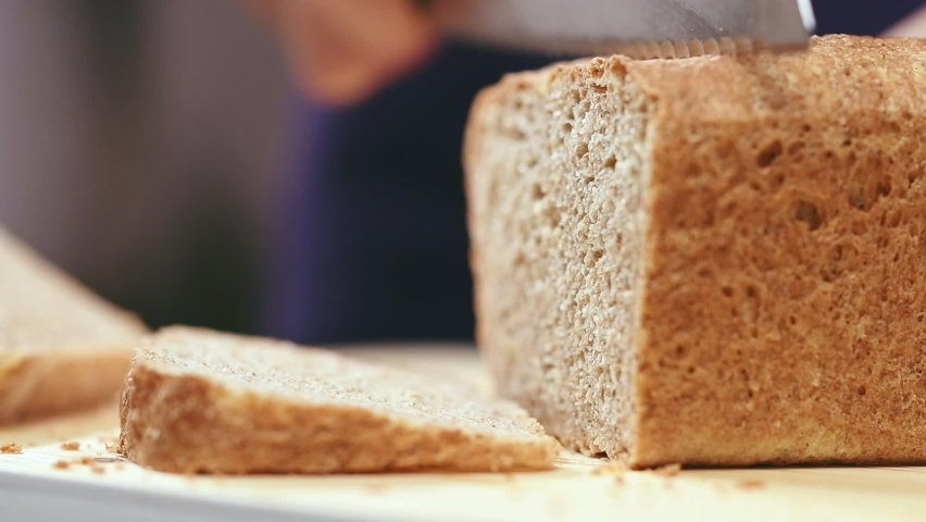 Slicing whole wheat bread on cutting board. Royalty-Free Stock Footage #1058659726