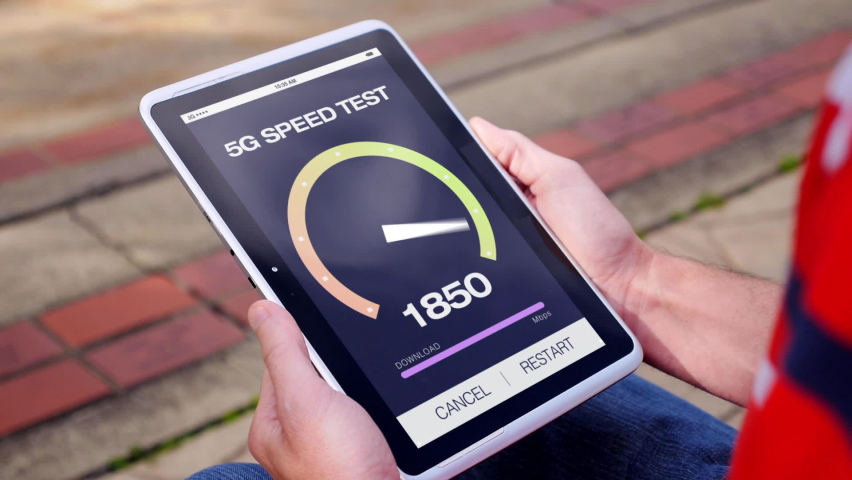 A man test his 5G high-speed wireless download speed on his tablet PC. Fictional interface speedometer gauge created in After Effects. | Shutterstock HD Video #1058660545
