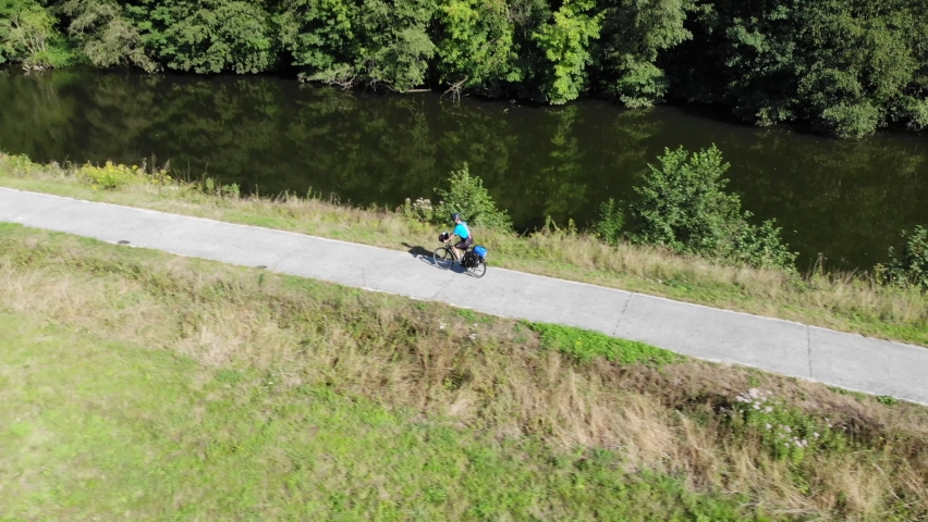 Drone view of male cyclist cycling on bike. man in cycling clothes is training on bicycle Cycling near Sambre / Meuse  Belgium canal cardio exercises outdoors. workout healthy lifestyle concep Royalty-Free Stock Footage #1058664991