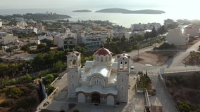 Flies to the right along a large Christian temple on the island of Crete in the evening, in the frame of the street, the sea in the background, aerial video