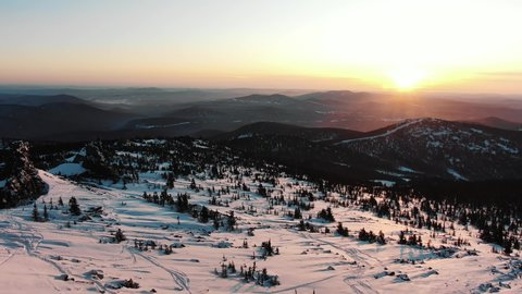 aerial motion above large mountain with numerous ski tracks on snowy slopes and pine trees at bright sunrise light in cold winter