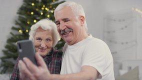 Handheld shot of happy elderly man and woman in sleepwear holding mobile phone and taking selfie or talking on video call with family on Christmas morning