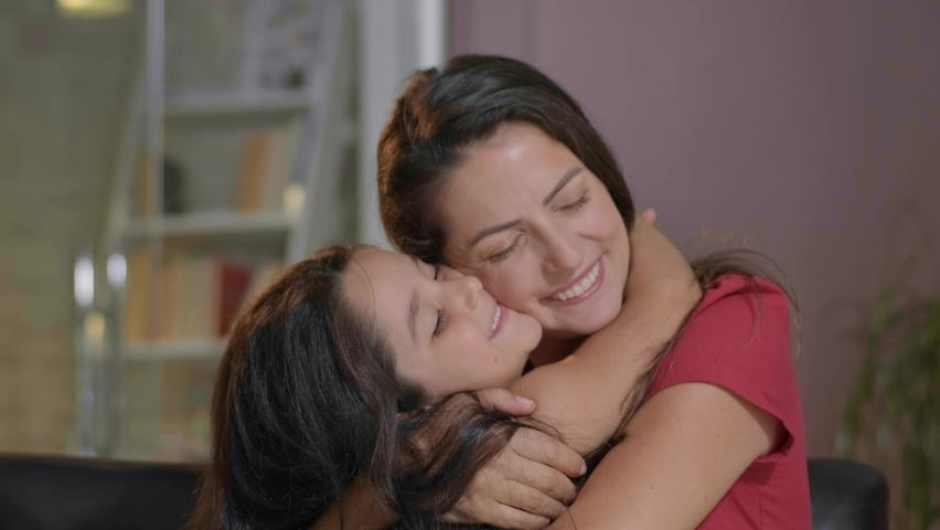 Portrait of a mother lovingly embracing her daughter. Her mother is hugging and kissing her daughter. Mother's Day concept.