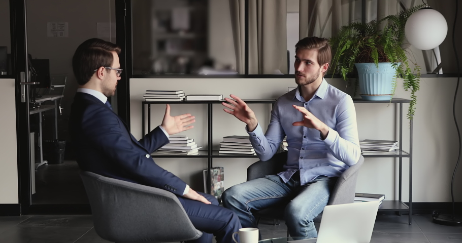 Young confident businessman discussing investment opportunity with financial expert in formal wear, seated on comfortable chairs in office. Smart startup owner consulting with lawyer at meeting.