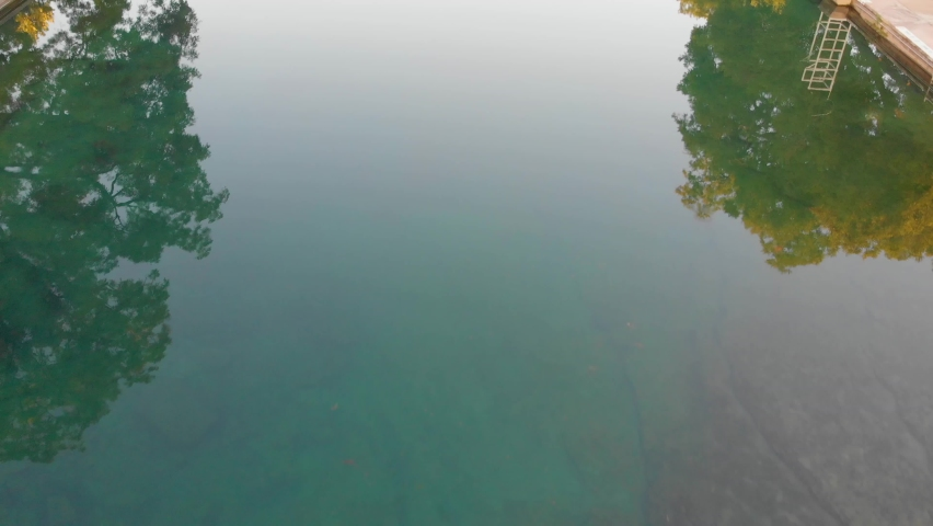 Top down shot of the crystal clear waters of barton springs pool. Slow pan up to downtown Austin Texas.