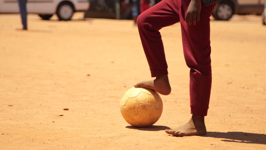 Medium close-up of young boy standing with his bare foot on soccer ball in dusty rural field of dirt before stepping back and kicking it on bright sunny day