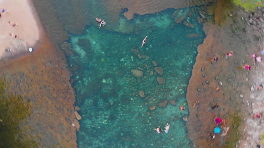 Top Down Drone shot of barking springs in Austin, TX. People and dogs being active in the water . Shot in Austin TX, August 2020