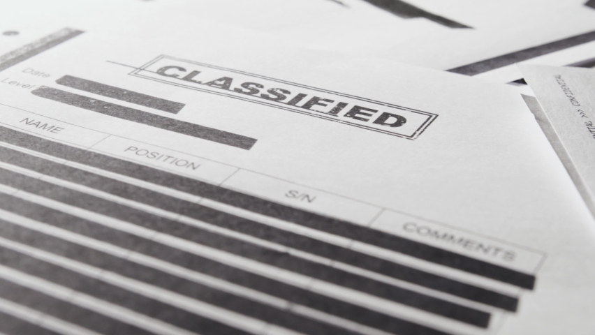 Pan across classified text documents and top secret censored information files. Leaked papers of covert activity and operations of military, army or government agencies. Close up of sensitive info. Royalty-Free Stock Footage #1058701111