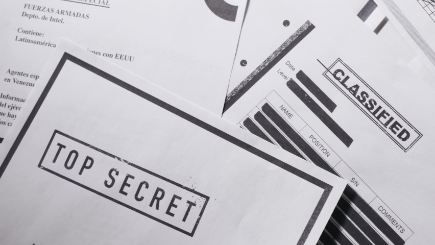 Top down shot moving across different secretive official important documents. Panning over papers with Top secret classified text and stamps with crossed and censored black lines. Exposed information. Royalty-Free Stock Footage #1058701117