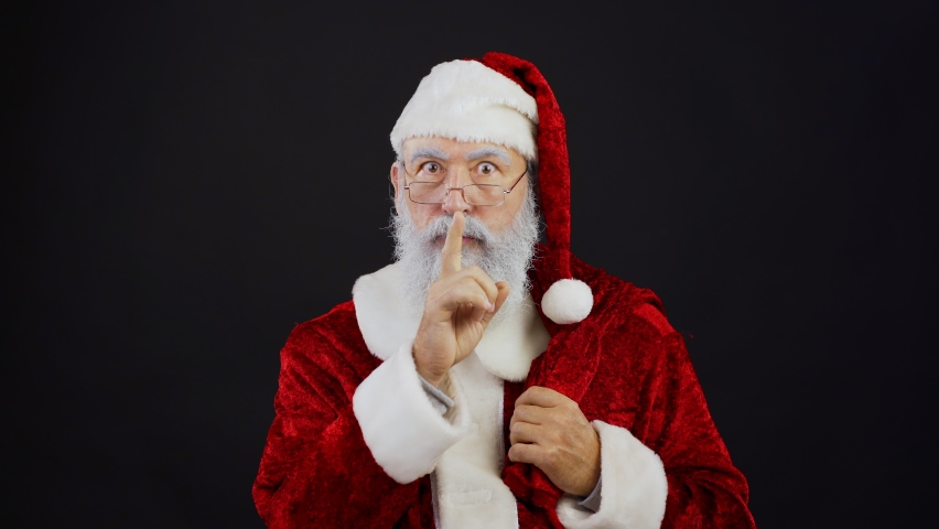 Waist up portrait of Santa Claus in traditional red costume, eyeglasses and with sack of gifts looking at camera and doing shh gesture putting index finger on lips standing against black background | Shutterstock HD Video #1058701237