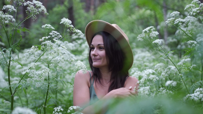 Young pretty woman in hat poses in deep forest among white flowers.