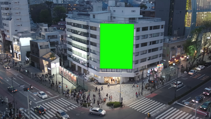 Large billboard with a green screen for advertising, on the modern building, busy crossroad with neon lights, traffic, crowd, Tokyo, Japan.  | Shutterstock HD Video #1058702794