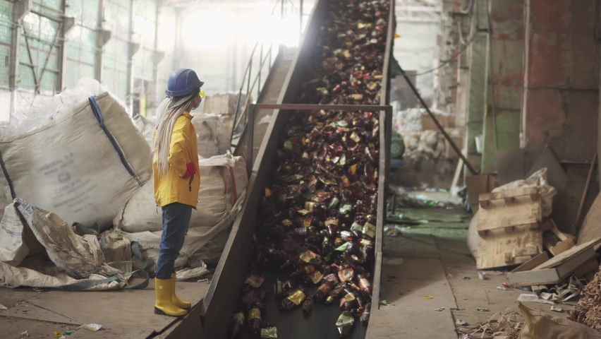 Woman-worker in yellow and transparent protecting glasses, hard hat and mask watching the conveyor full of used plastic bottles lifting up. Footage of automized process on recycle plant | Shutterstock HD Video #1058704270