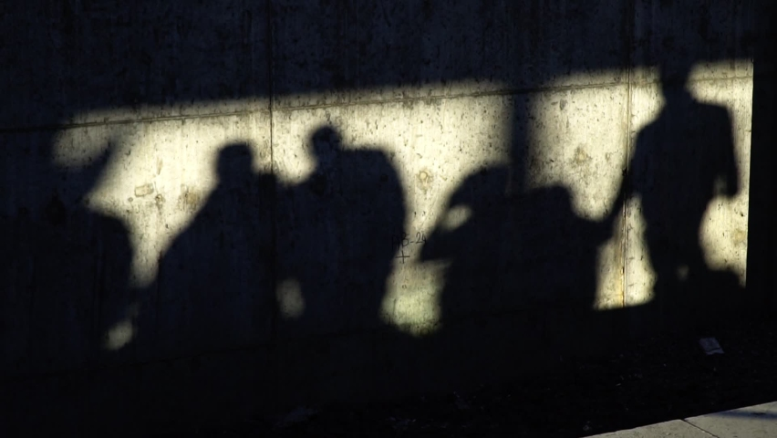 Shadows of the people on a concrete wall in slow motion Royalty-Free Stock Footage #1058709826