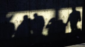 Shadows of the people on a concrete wall in slow motion