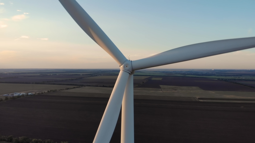 Drone flying away of wind power turbine rotating rotor blades with agricultural fields at dusk sunset. Renewable energy source windmill electric power production in Odessa Ukraine   Shutterstock HD Video #1058710570