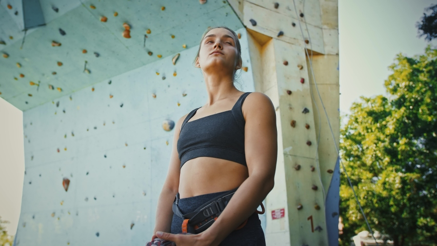 Young woman alpinist holding climbing rope at outdoor gym wall, tracking shot