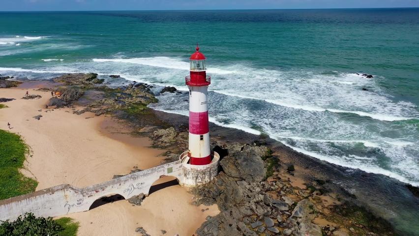 Itapua Lighthouse, Salvador, Bahia, Brazil. Beach Tropical Travel. Lighthouse, Salvador, Bahia. Coastal Beach. Caribbean Beach. Vacation Seaside. Caribbean Lighthouse Maritime Navigation Seaside Ocean Royalty-Free Stock Footage #1058716294