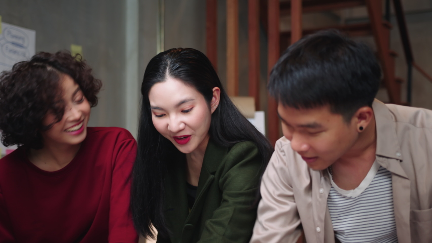 Group of Asian Business people  giving high five celebrating successful business achievement, winning, receiving good feedback or results from client in a creative loft office workplace.