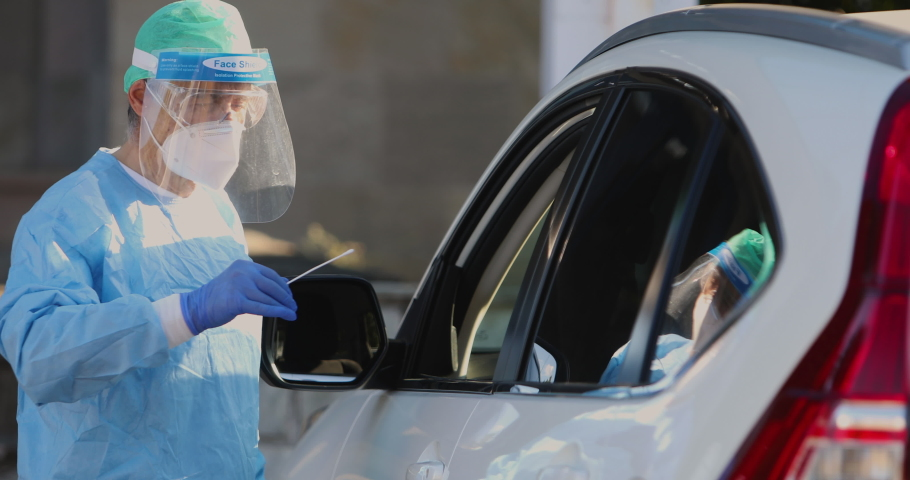 Medical personnel wearing a PPE, performing PCR with a swab in their hand, on a patient inside his car to detect if he is infected with COVID-19 Royalty-Free Stock Footage #1058725687