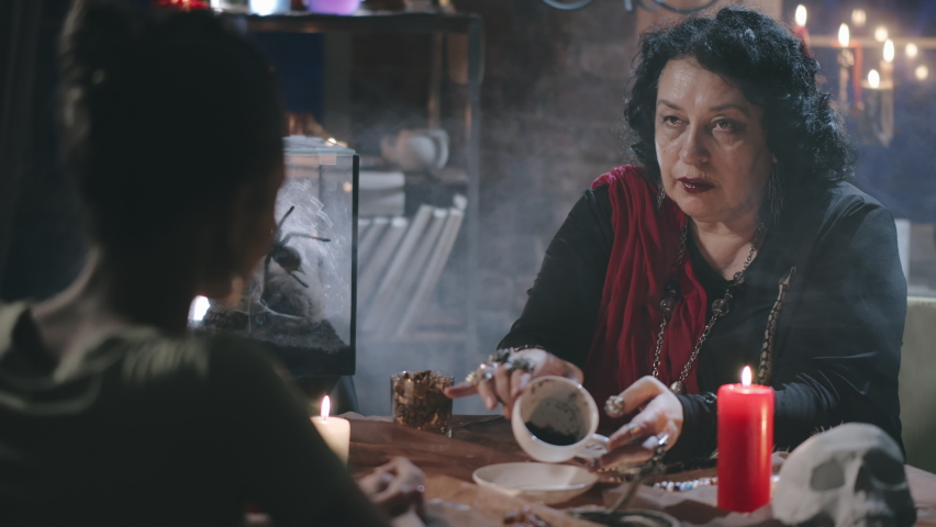 Woman fortune teller looking in empty coffee cup of client and reading future. Old seer divines on coffee grounds of young female customer. | Shutterstock HD Video #1058726422