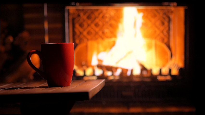 A cup of hot tea in front of the fireplace on a cozy evening. Festive mood Royalty-Free Stock Footage #1058726758