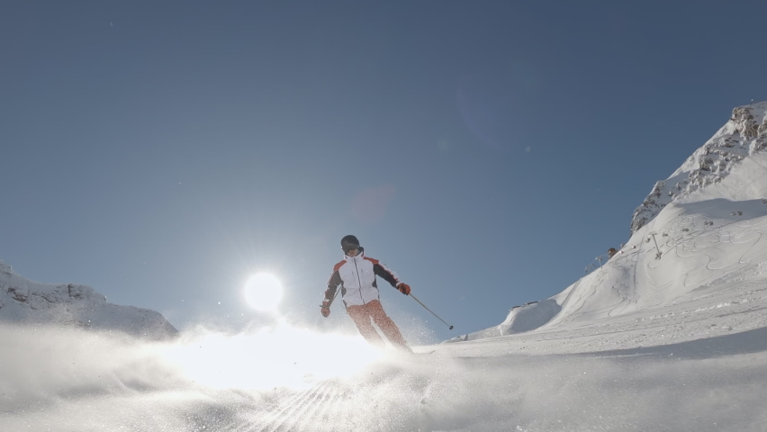 One Man downhill skier slowly down the ideal ski slope. Skiing on the track against the backdrop of picturesque snow-capped mountains. Winter outdoor activities. Slow motion, 2K RAW footage, 2704x1520 | Shutterstock HD Video #1058726770