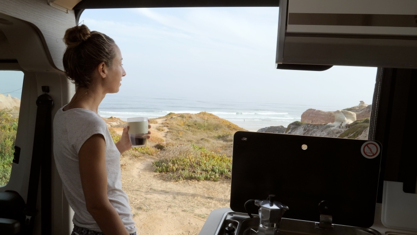 Young woman having a fresh cup of coffee in her camper van enjoys coastal views from her vehicle. Female solo traveller living in her van drinking coffee in the morning  Royalty-Free Stock Footage #1058727025