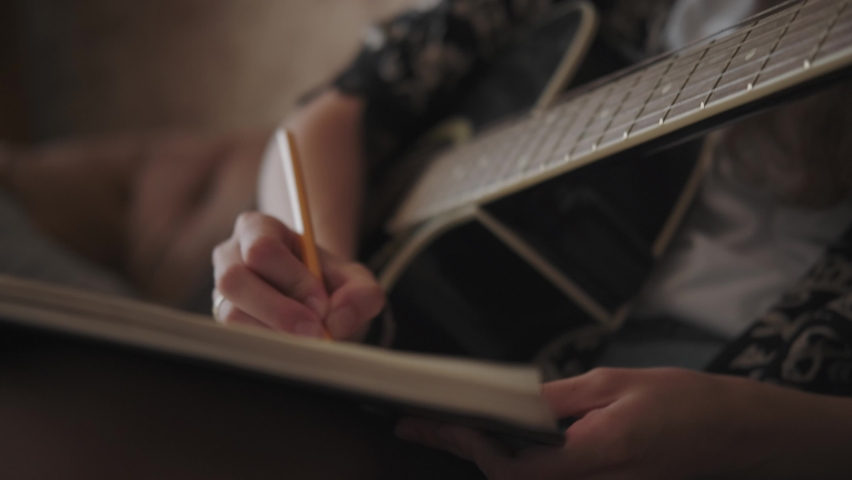 Creative female musician with guitar alone writing song, composing music sitting on sofa in bright day room. A woman plays the guitar, stops and writes text or notes in a notebook. To compose music | Shutterstock HD Video #1058727103