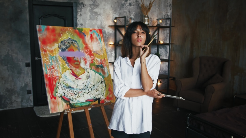 Female painter is holding paintbrushes and palette while posing by newly painted portrait in modern art style | Shutterstock HD Video #1058729185