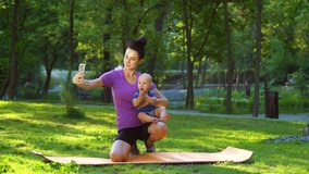 Fit woman in sportswear sitting in park and recording video with smartphone while holding baby in arms. Fitness blogger with her little child streaming from public park. Concept of technology