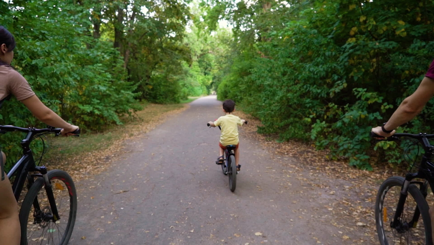 Little boy and parents biking in summer park, green trees on sides. Following shot fit family riding bicycles and enjoying outdoor activity. Concept of sport | Shutterstock HD Video #1058729569