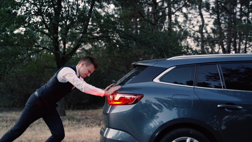 Side view of a Man pushing broken car, vehicle with trouble. young Man in business suit pushing a broken car.  Pushing a broken down car | Shutterstock HD Video #1058731165
