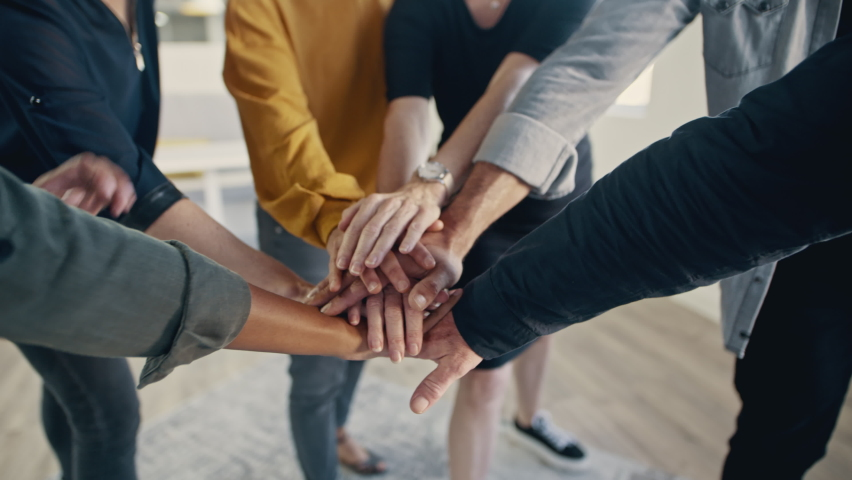 Multi-ethnic businesspeople putting their hands on top of each other and clapping. Business team making a stack of hands showing unity.  Royalty-Free Stock Footage #1058735134