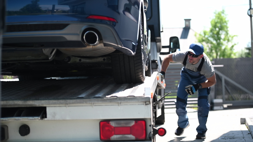 Tow Truck Male Driver Checking And Securing Car On Top Of Flatbed Towing Trailer. Car Transporter Ready To Depart. Royalty-Free Stock Footage #1058735455