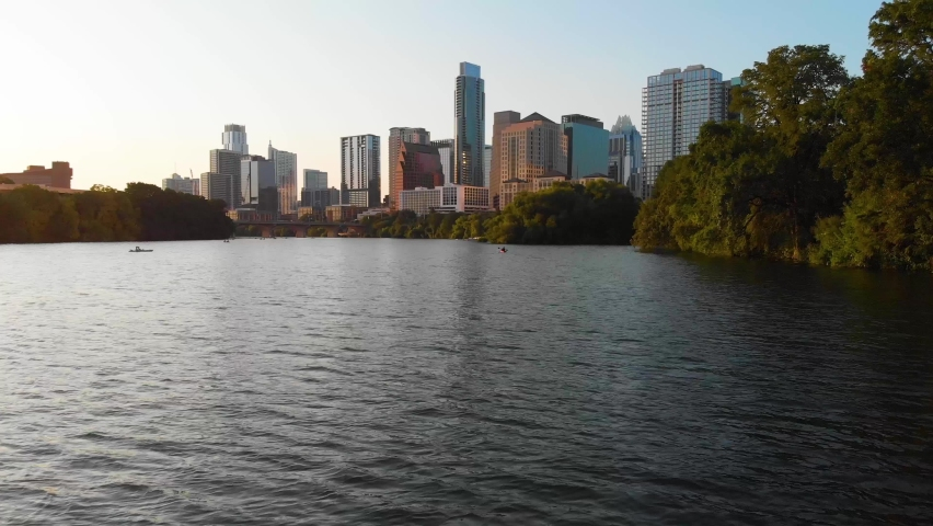 Low drone shot of a Kayaker paddling towards Downtown Austin Texas. Shot August 2020