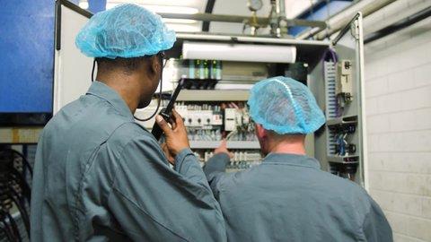 Two industrial workers check an industrial meter cupboard