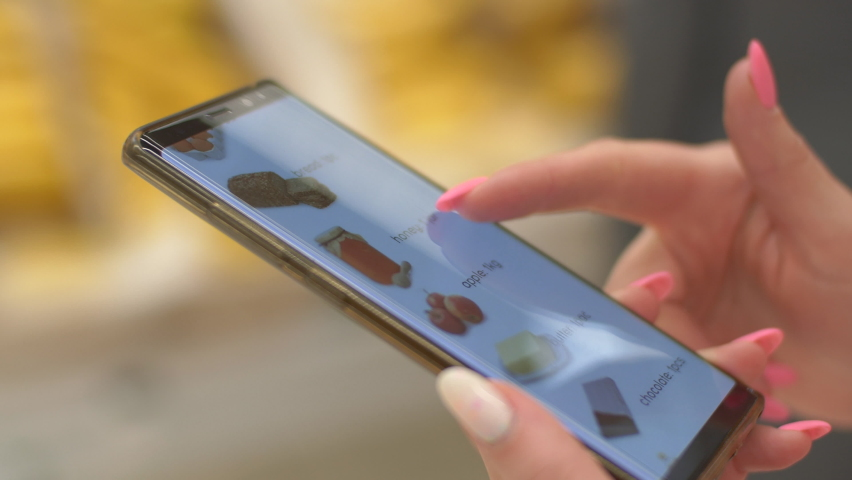 Close-up Side View Female Purchaser Looking Shopping List in Smart Phone Inside Grocery Store. Person Reading Check List on Display in Healthy Lifestyle App Indoors Marketplace. Scrolling Mobile Phone. Royalty-Free Stock Footage #1058749714
