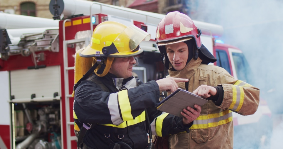 Medium plan of two firefighters discussing rescue plan looking at tablet while standing in helmets near a fire van. Smoke from the fire covers rescuers and a fire truck. | Shutterstock HD Video #1058752333