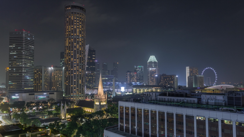 Singapore skyline with St. Andrew's Cathedral aerial night timelapse hyperlapse. It is an Anglican cathedral in Singapore, the country's largest cathedral. Skyscrapers on a background Royalty-Free Stock Footage #1058753905