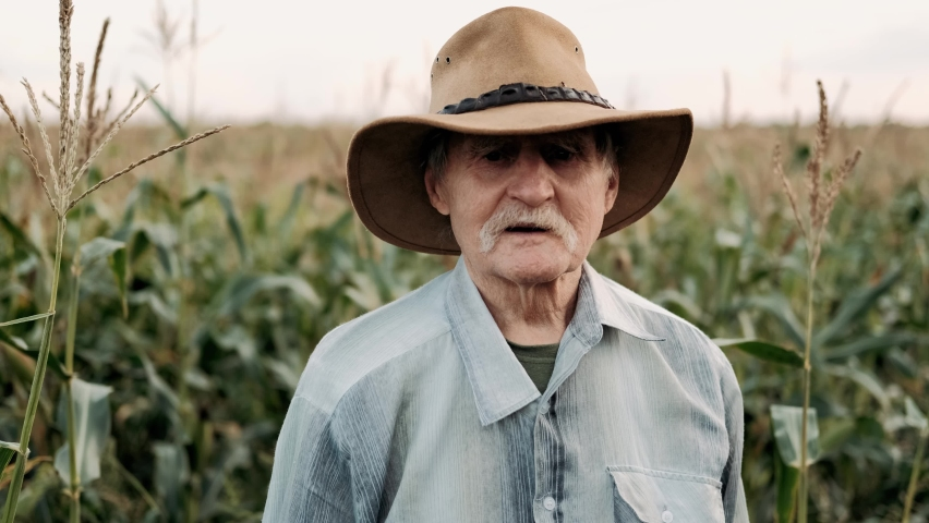 Portrait of a Senior adult farmer in hat in a field of corn looking at the camera and smiling at sunset. Face Happy Farmer Worker summer nature Farming Real people Concept | Shutterstock HD Video #1058758495