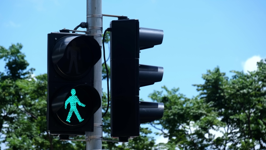 Traffic light turns from red to green at financial district intersection.