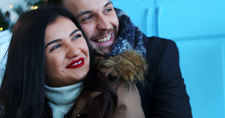 Romantic New Year and Christmas concept. Closeup happy young couple hugging and smiling. They celebrate for two in front of a Christmas decorated house. 4k Slow motion