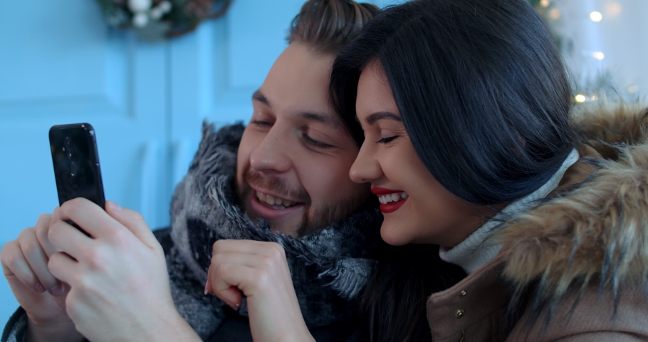 Romantic New Year and Christmas concept. Closeup happy young couple looking at a smartphone. They celebrate for two in front of a Christmas decorated house. 4k Slow motion